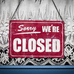 Sorry we're closed sign in window with lace curtains